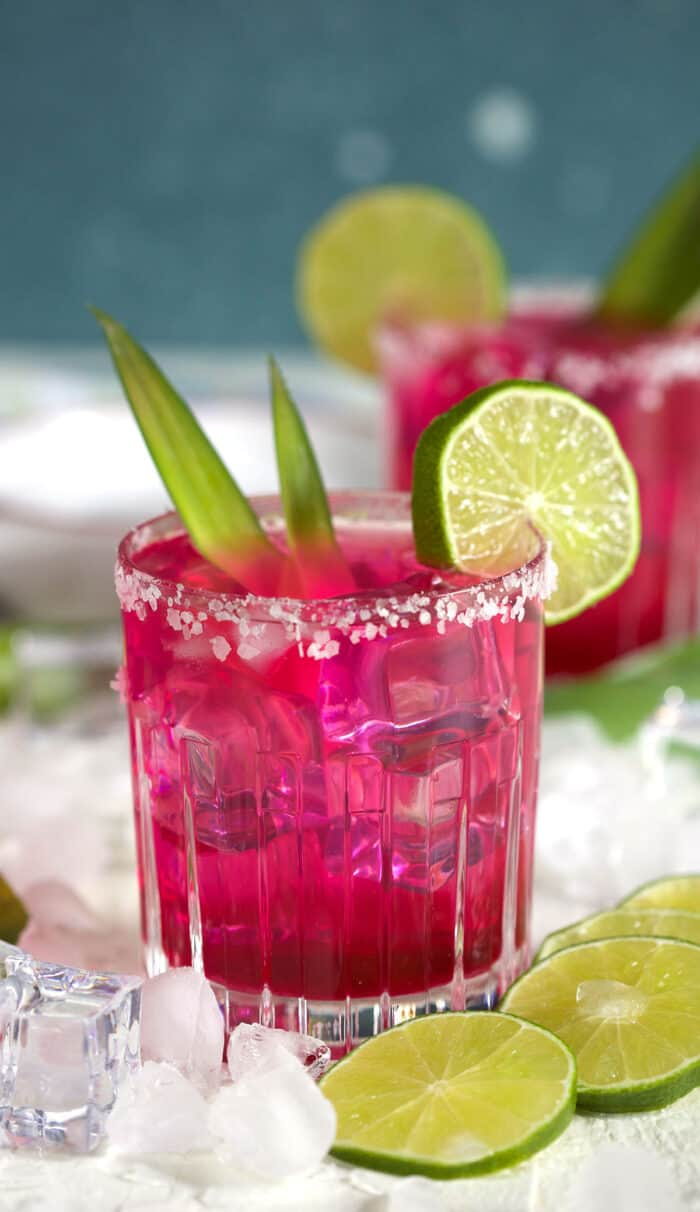 A glass filled with margarita is ready to be enjoyed on a white surface.