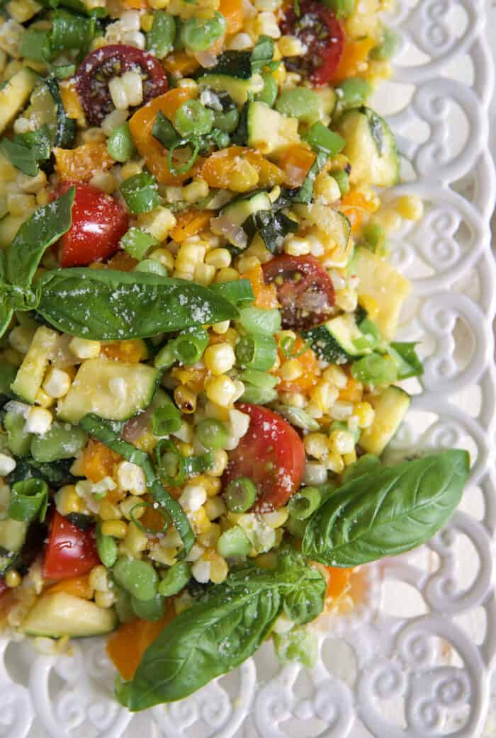 A serving of corn succotash is presented on a white platter.