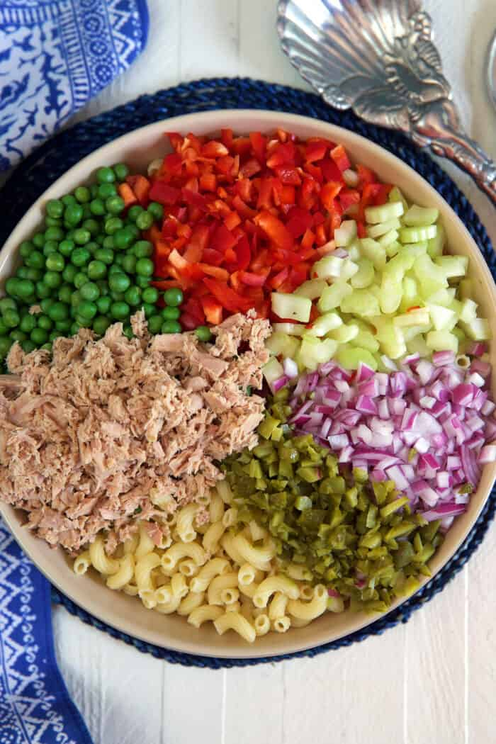 Ingredients for macaroni salad are in a large bowl.