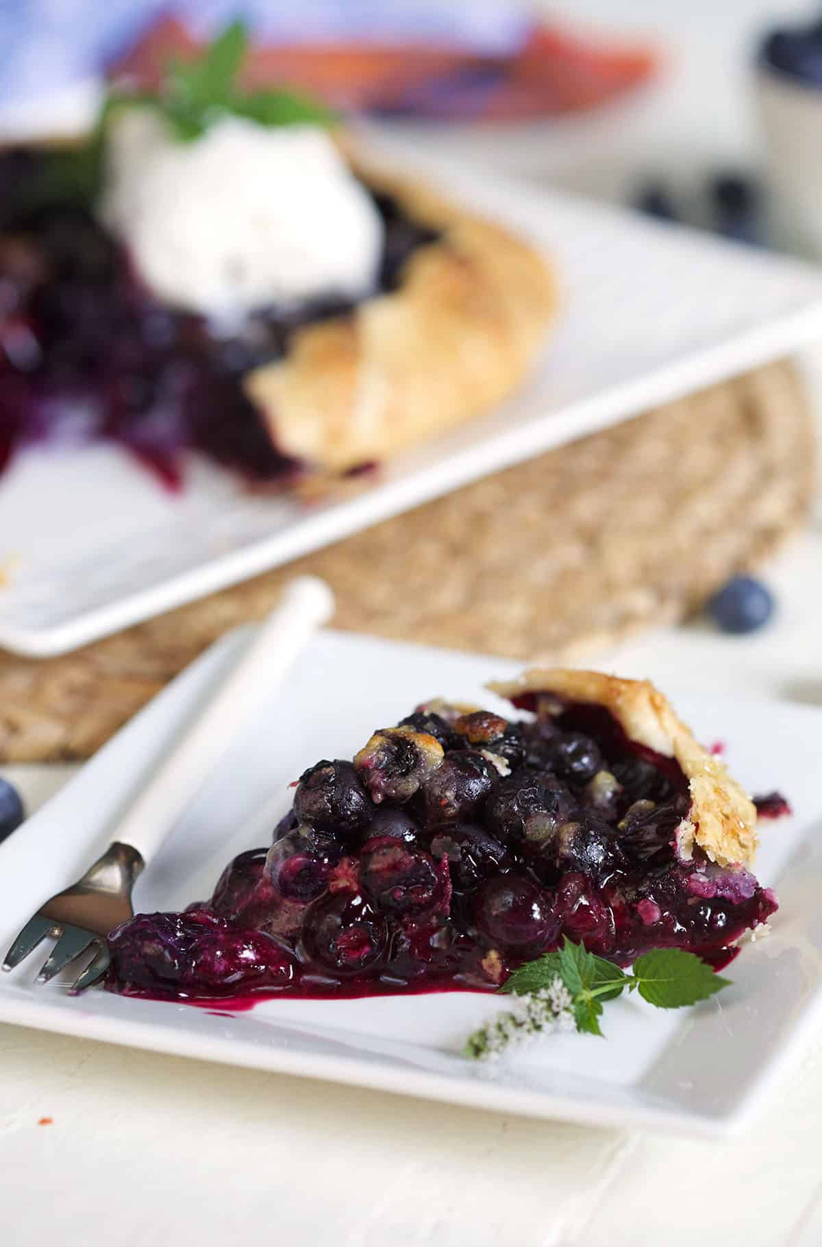 Slice of blueberry galette on a white plate