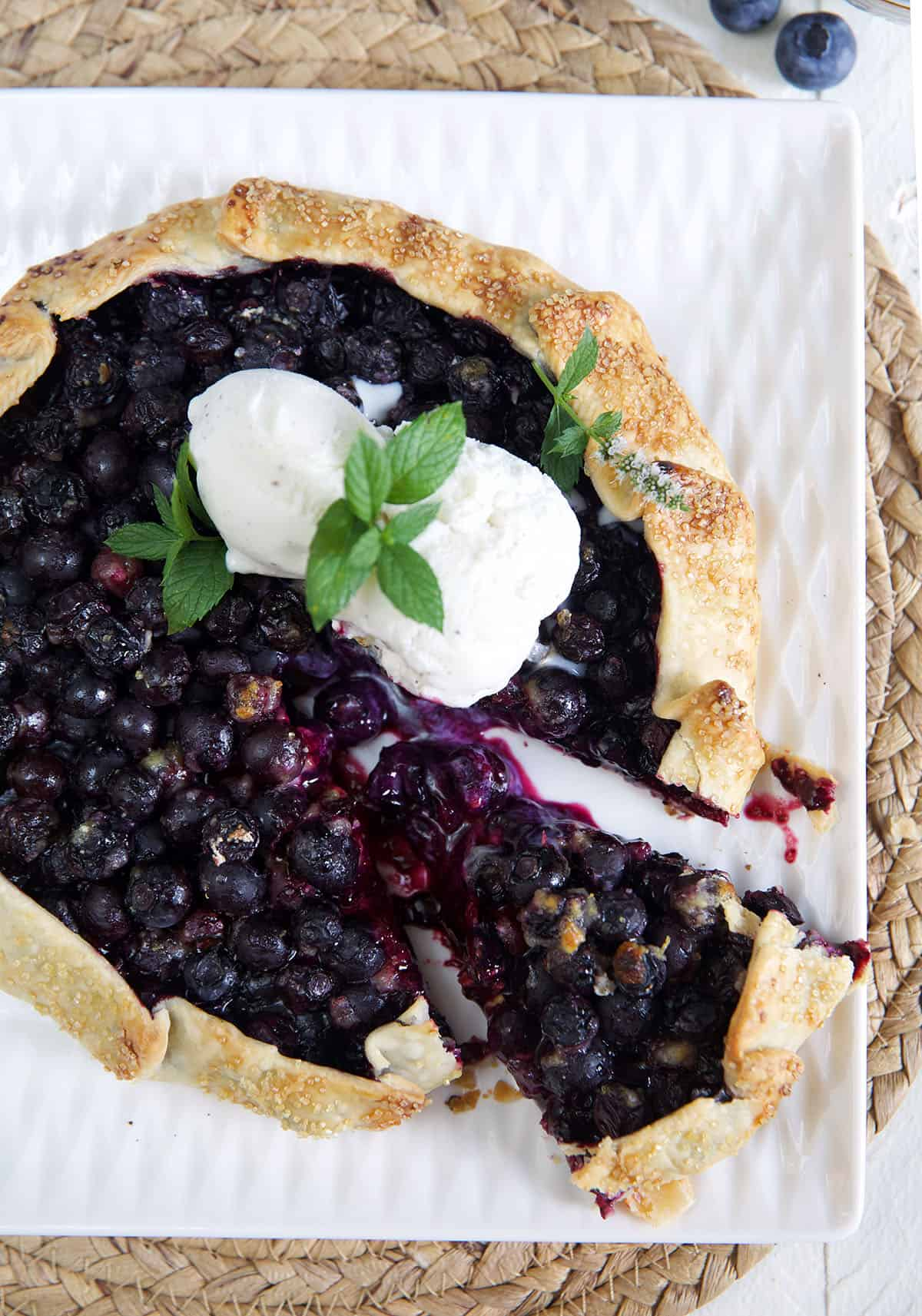 Blueberry Galette with ice cream on top and a wedge cut out of it.