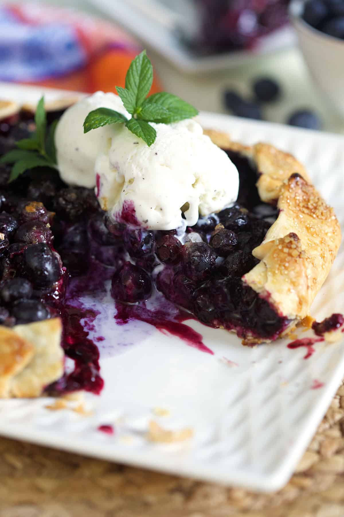 Blueberry Galette with vanilla ice cream on top and a sprig of mint on top.