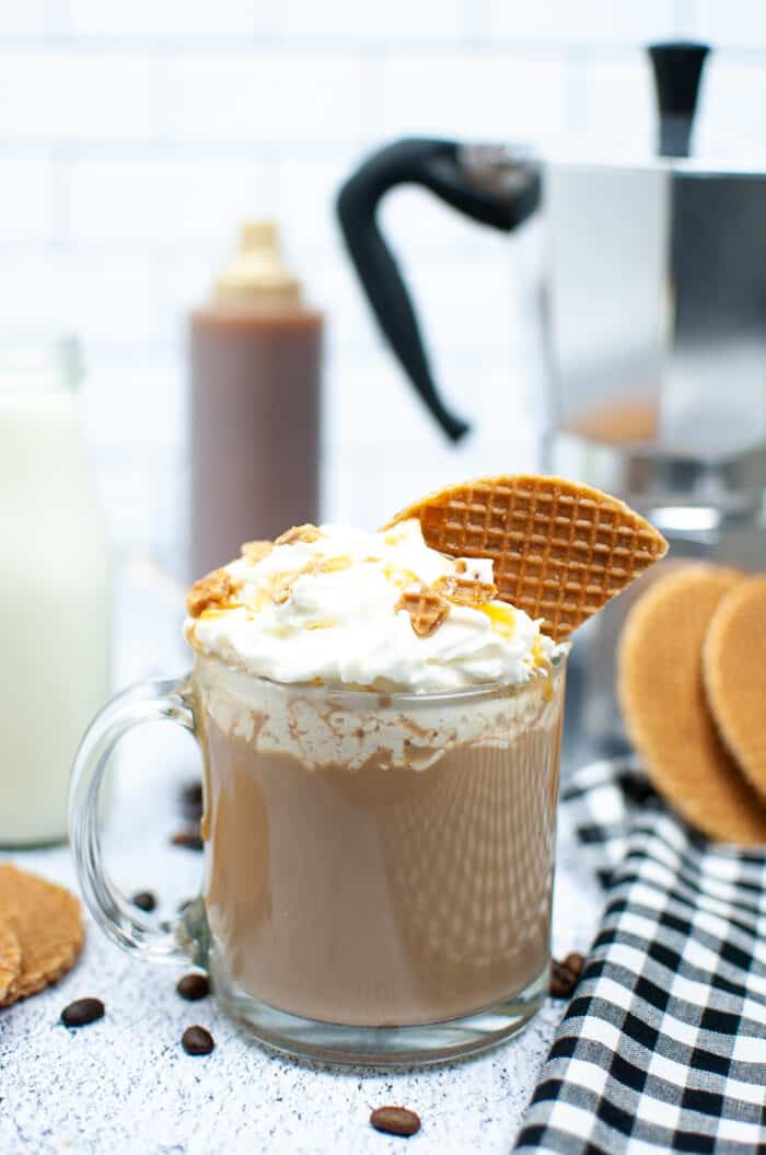 A latte is topped with whipped cream and a piece of waffle cone on a white surface.