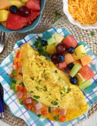 An omelette and fruit are on a plate.