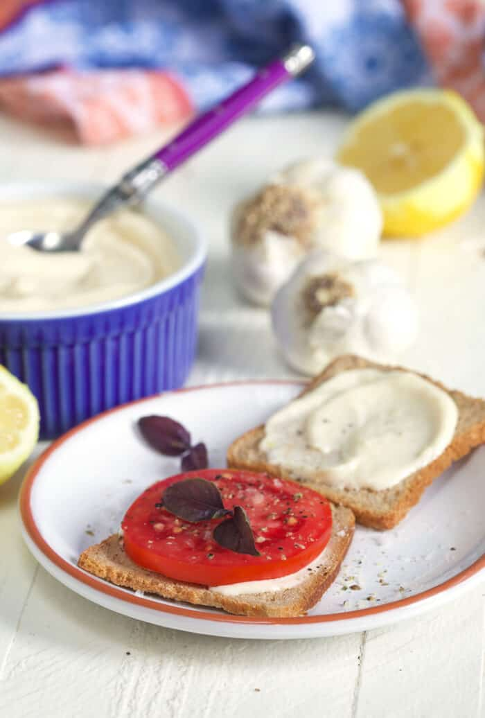 Tomato on a small slice of bread with aioli spread on a second slice on a white plate.