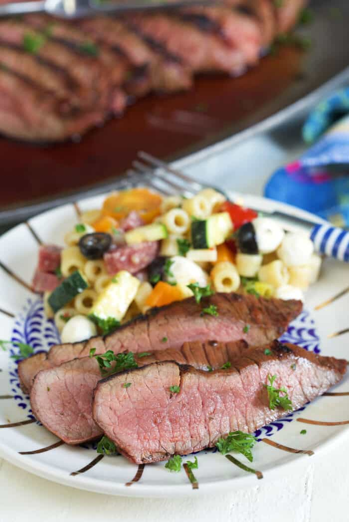 Several pieces of steak are plated with pasta salad.