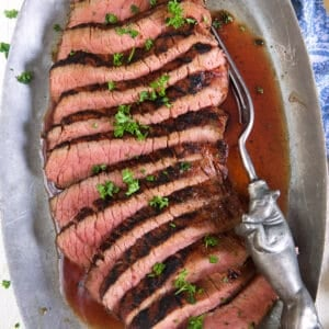 Sliced red meat is presented on a silver platter.