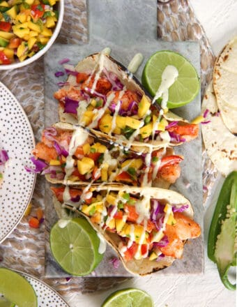 Three lobster tacos are placed on a table next to halved limes.
