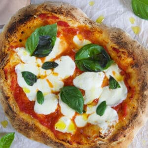 A pizza is garnished with basil leaves.