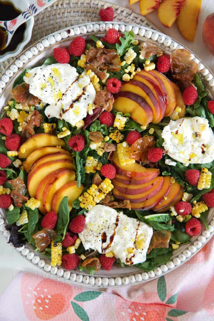 A peach salad in a large serving bowl is drizzled with hot honey.