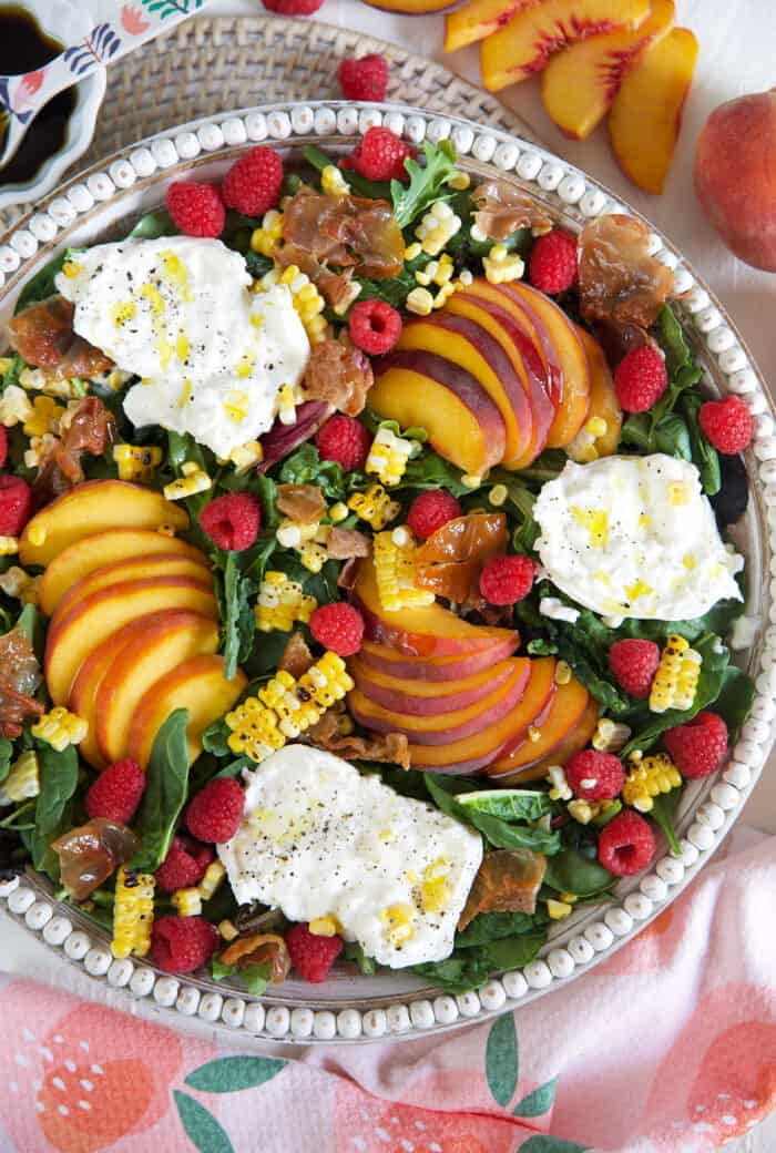A large white serving bowl is filled to the brim with peach burrata salad.