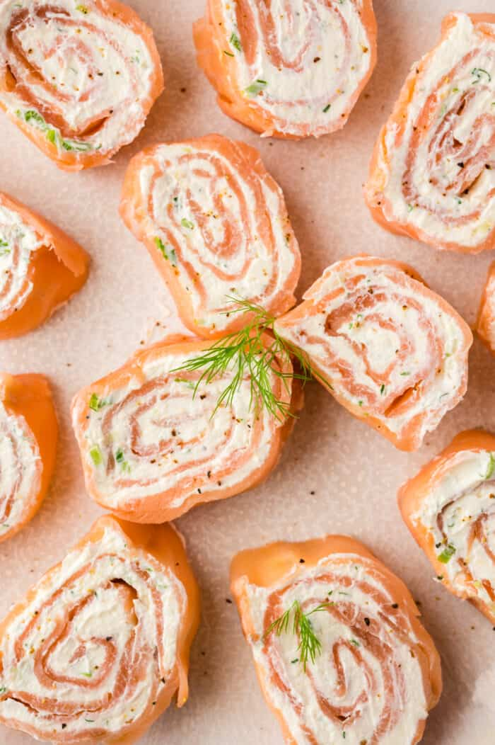 Several smoked salmon pinwheels are placed on a tan surface.