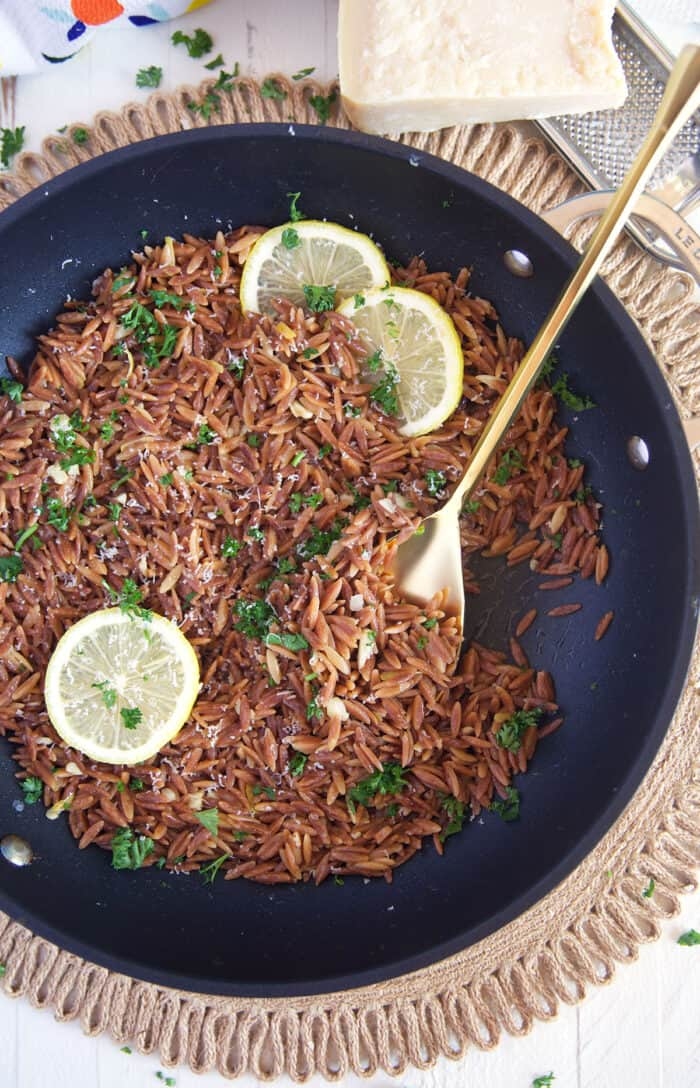 Cooked orzo is topped with fresh parsley in a skillet.