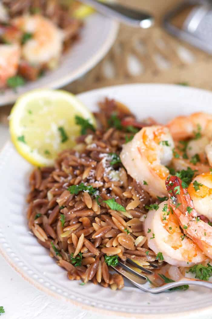 Shrimp, orzo and fresh lemon slices are all in a white bowl.