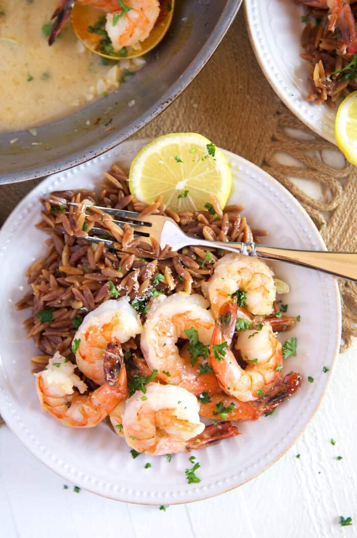 Orzo and shrimp are both placed in a white bowl with a lemon wedge.