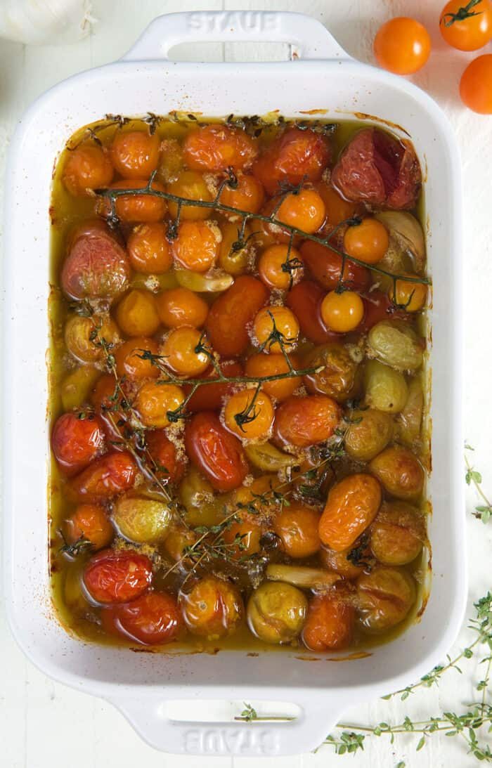 Tomatoes baked in oil are presented in a large white casserole dish.