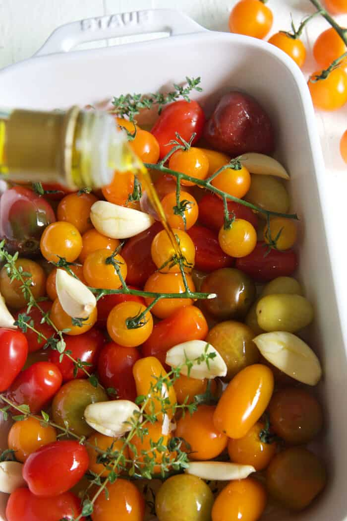 Olive oil is being drizzled over garlic cloves and tomatoes.