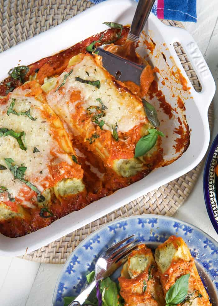 Manicotti stuffed pasta is being removed from a white baking dish.