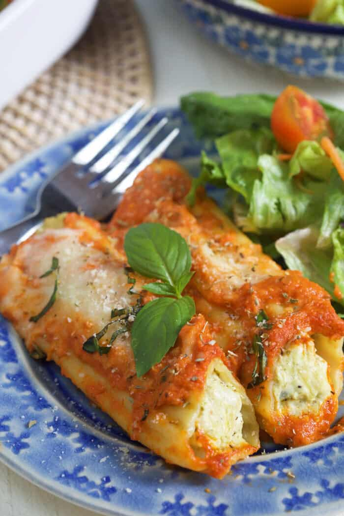 Two pieces of manicotti are placed on a plate next to a fork and side salad.