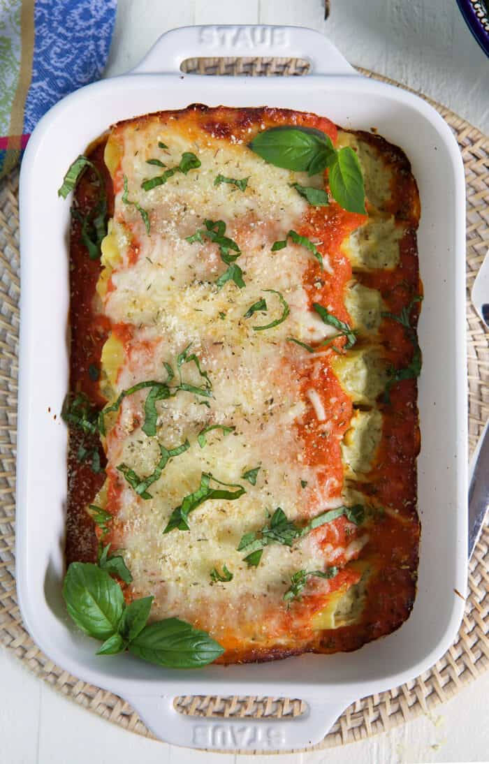 A white baking dish is filled with baked stuffed manicotti.