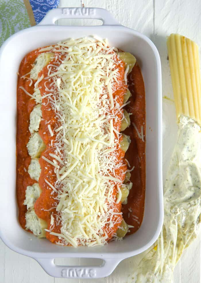 Stuffed manicotti is covered in uncooked cheese and sauce.