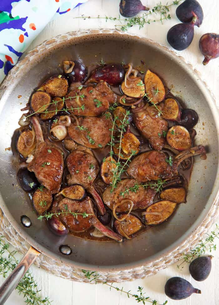 Lamb, figs, and herbs are cooking in a large metal pan.