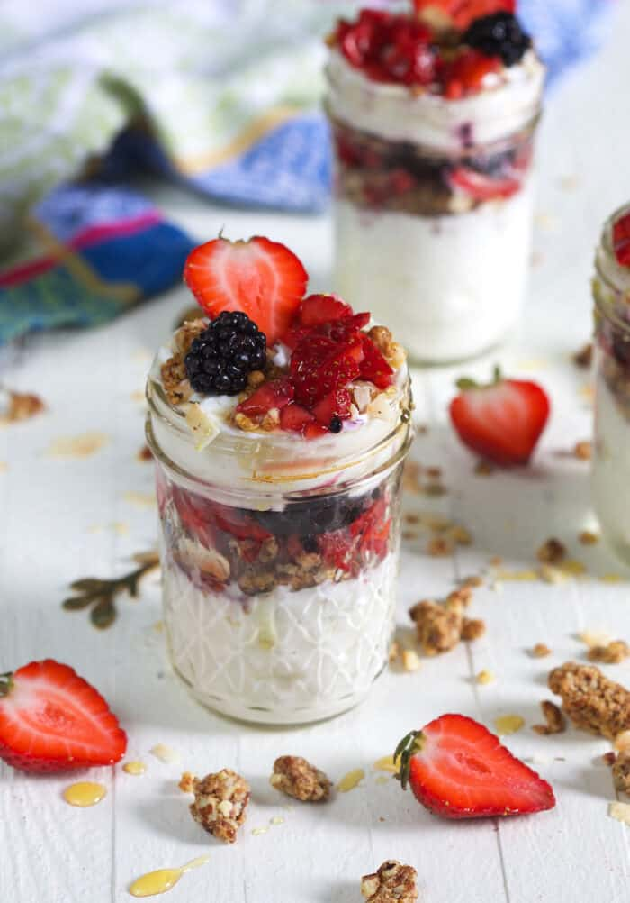 Two jars filled with parfait are placed on a white surface.