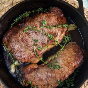 Two steaks are cooked with herbs and butter in a black cast iron skillet.