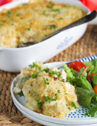 Chicken Divan casserole on a white plate with a casserole dish in the background.