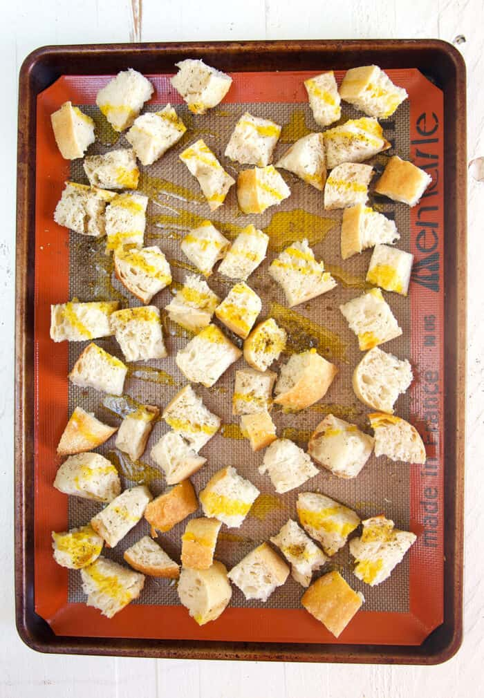 Croutons are drizzled with olive oil on a baking sheet and not yet cooked.