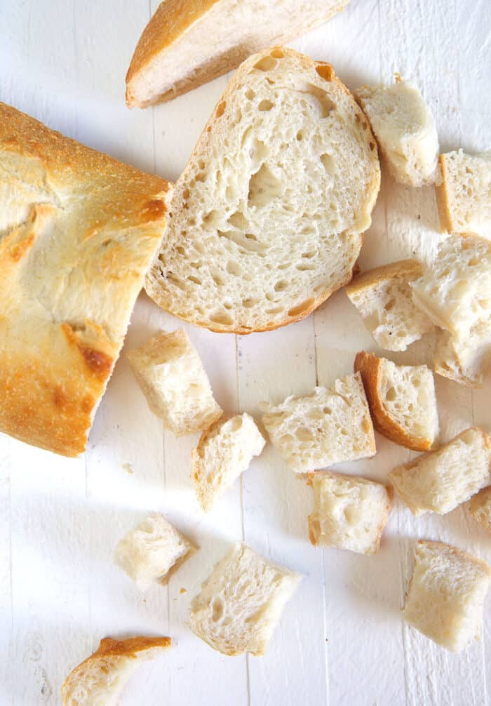 A loaf of bread is being broken up into bite sized pieces.