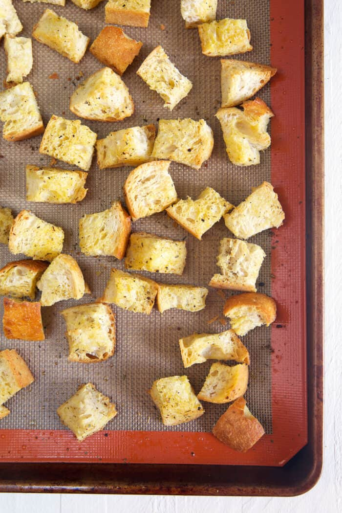 Homemade croutons are baked on a prepared baking sheet.