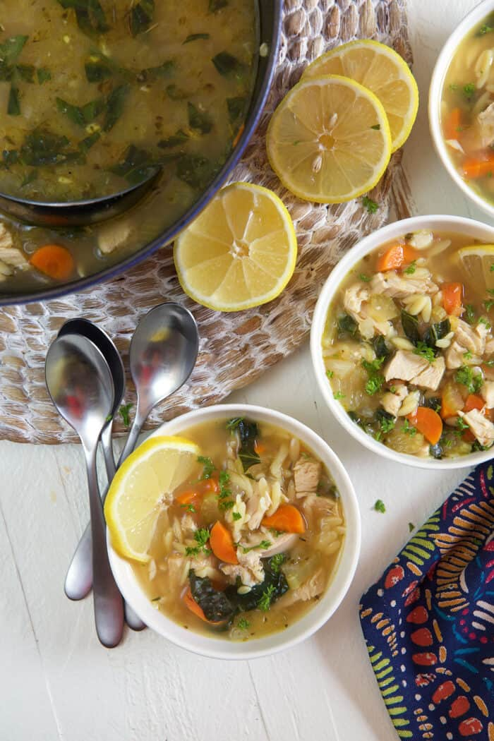 Two bowls of soup are placed next to a pretty full pot.