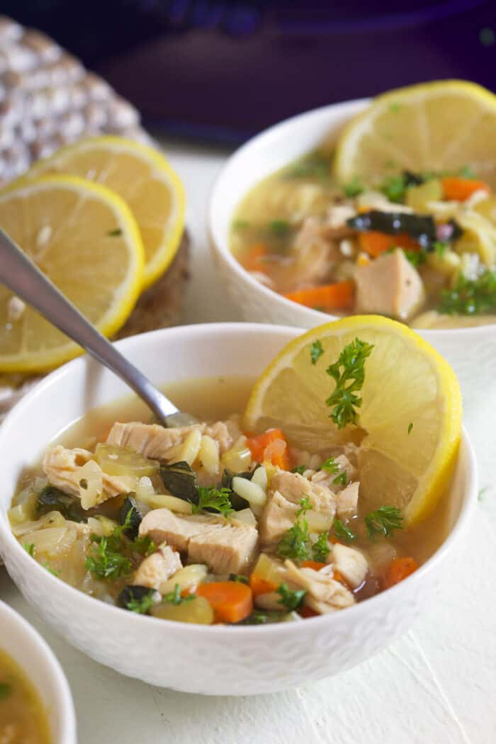A full bowl of soup is garnished and a spoon is placed in the bowl.