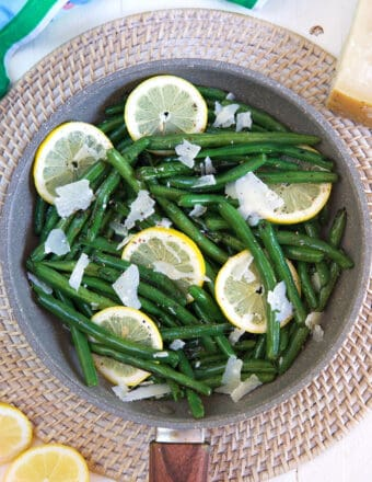 A pan of cooked green beans contains grated parmesan cheese and lemon slices.