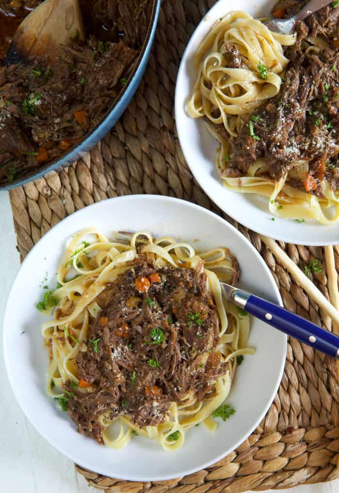 Two bowls of pasta and short rib ragu are placed on a brown place mat.