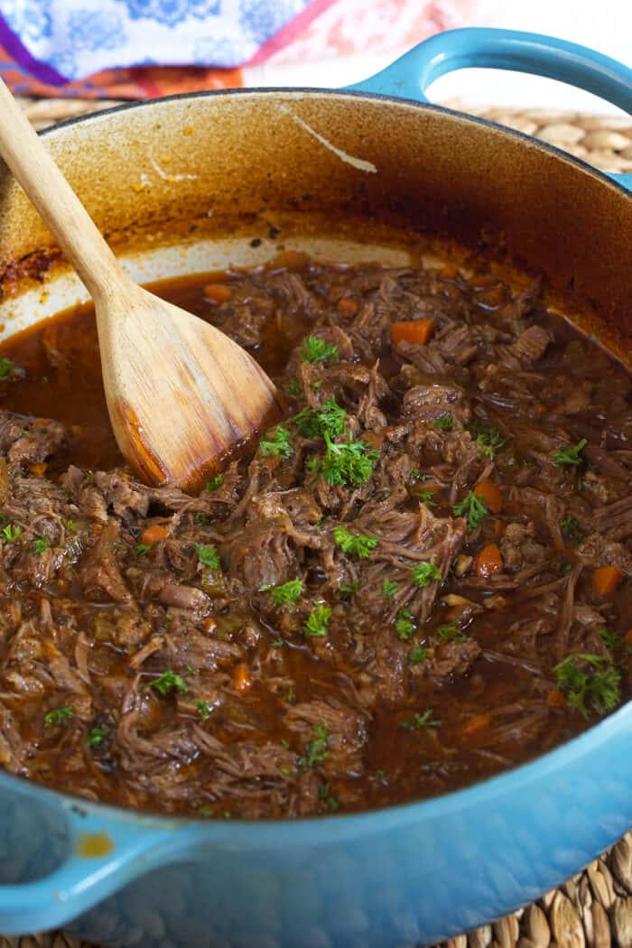 A wooden spoon is stirring parsley sprinkled braised and shredded meat in a pot.