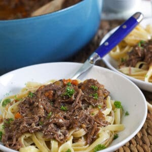 A blue fork is placed in a white bowl filled with noodles and short rib ragu.
