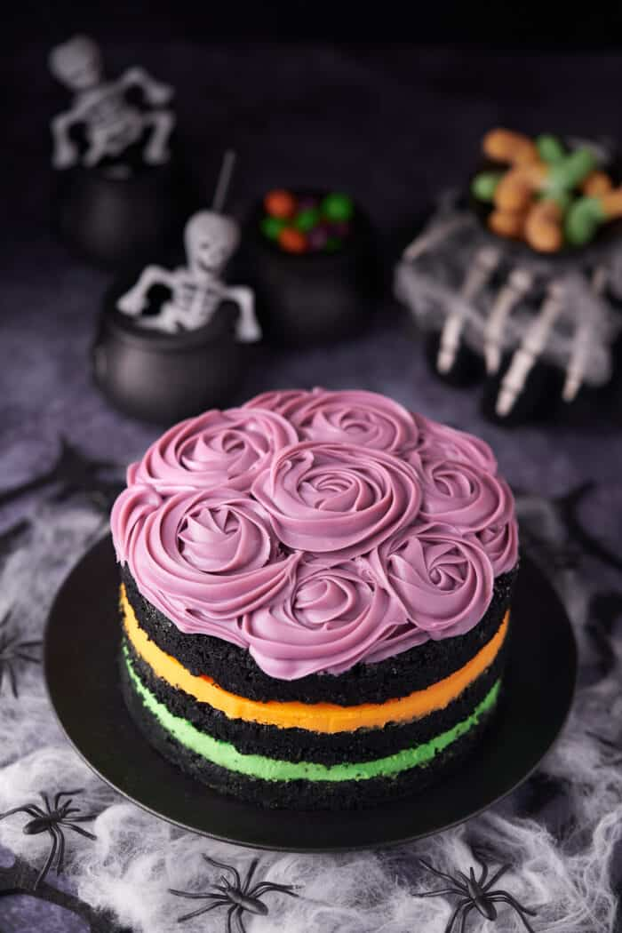 A layered cake is topped with purple icing. Skeletons are in the background.