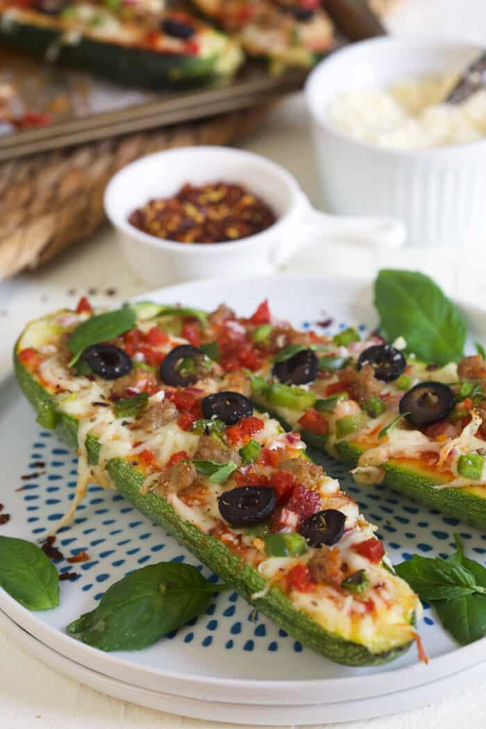 Two pizza zucchini boats are placed on a spotted plate.
