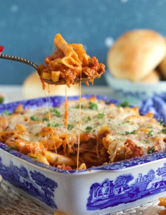A serving of mostaccioli is being lifted from a blue and white baking dish.