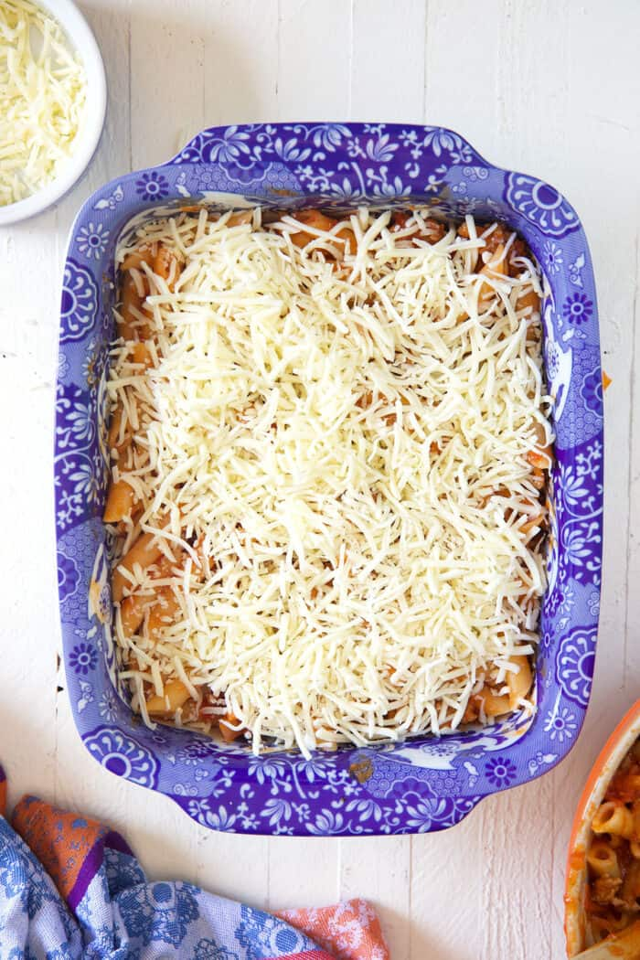 Shredded cheese is sprinkled evenly on top of saucy pasta in a baking dish.