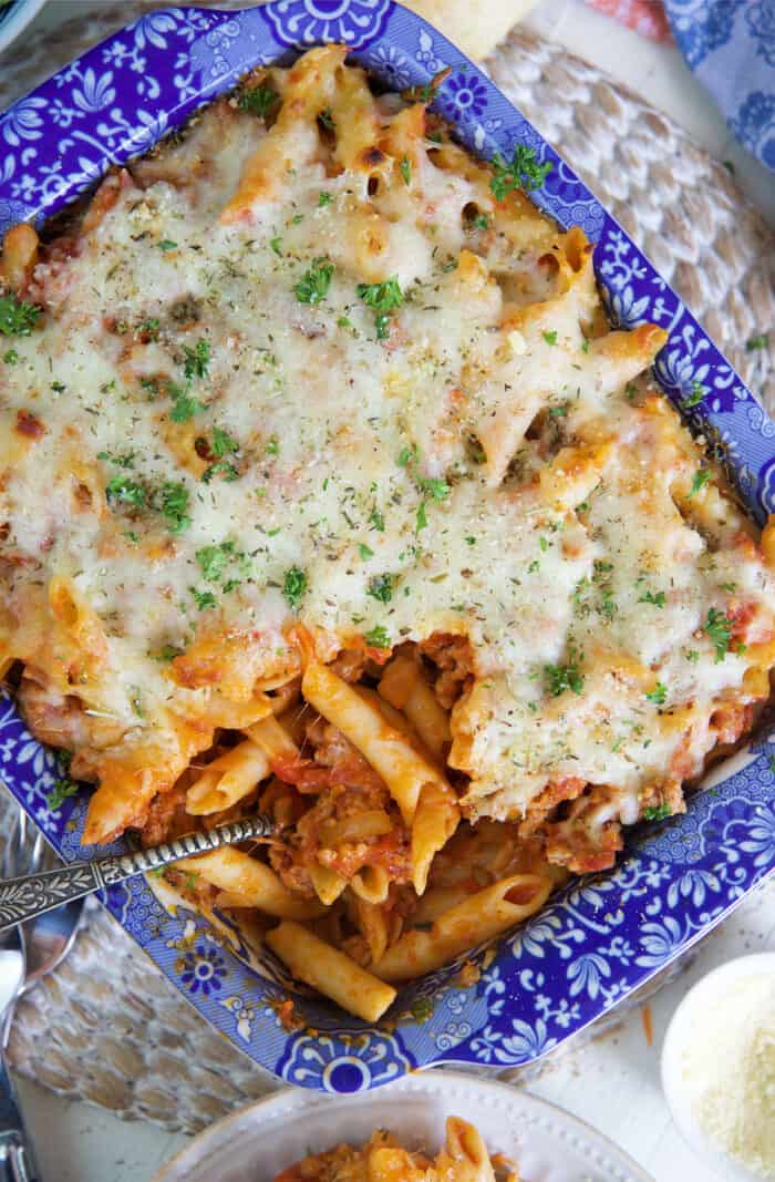 A serving spoon is placed in a dish filled with baked mostaccioli.