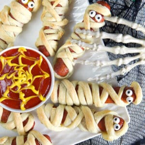 Mummy hot dogs are placed on a white plate with ketchup and mustard in the middle.