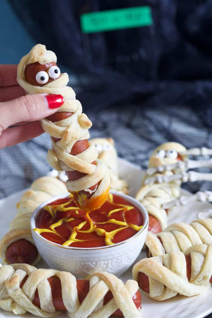 A mummy hot dog is being dipped into ketchup.