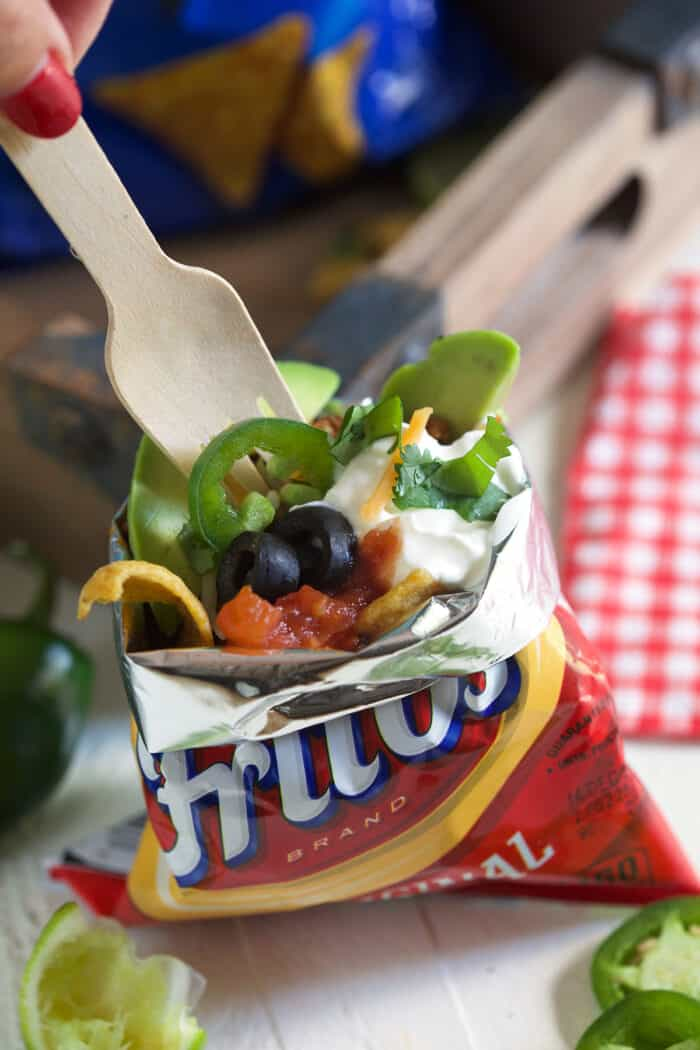 A fork is digging into a bag of frito's that's filled with all sorts of taco ingredinets.