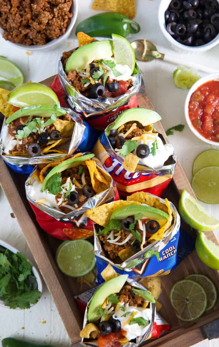 Several chip bags are filled with taco ingredients.