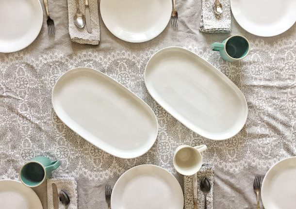 set table with white plates and gray tablecloth