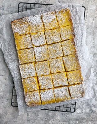 lemon bars on parchment paper and cooling rack with powdered sugar on top