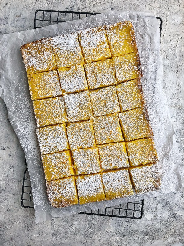 lemon bars on parchment paper and cooling rack with powdered sugar